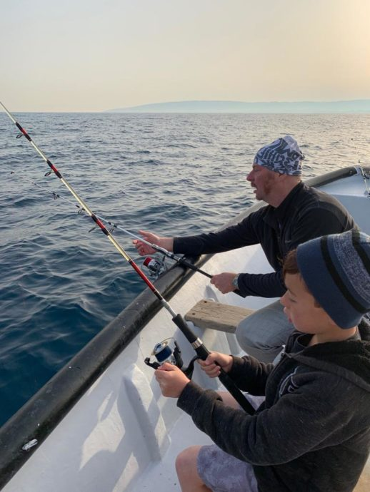 A man and a boy are fishing in a private boat in the Mediterranean Sea
