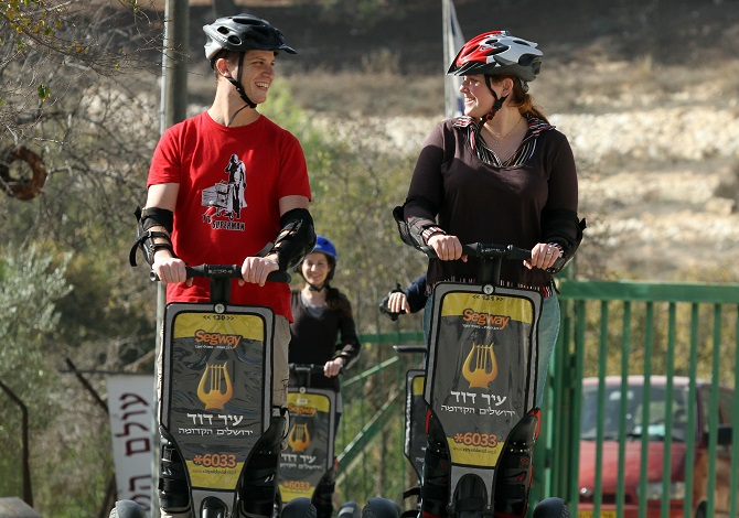 A boy and a girl each riding a Segway in the City of David in Jerusalem