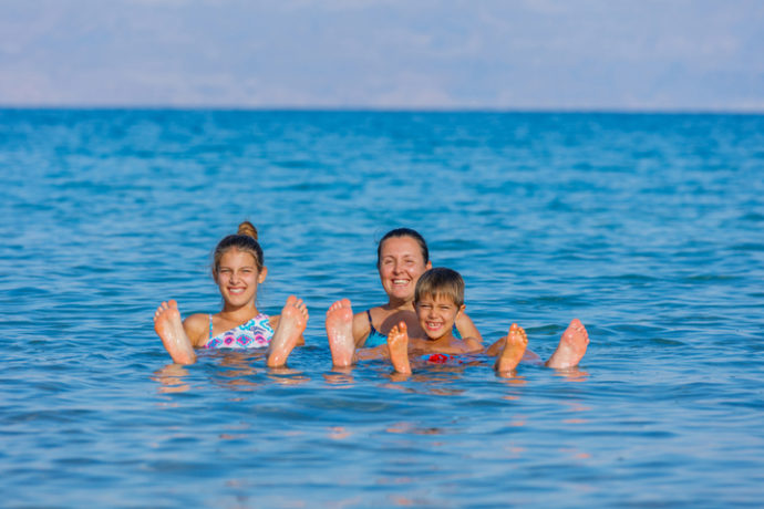 Family floating in Dead Sea