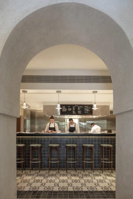 Professional chefs preparing various dishes at Golda Delicatessen restaurant.