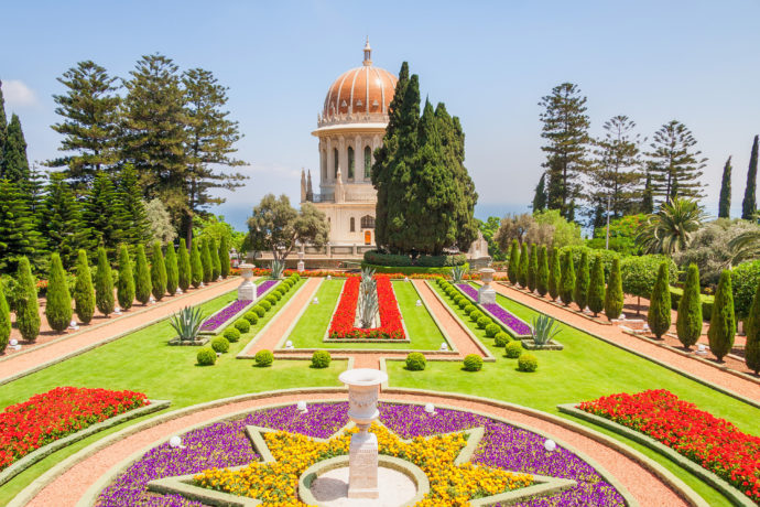 The Shrine of the Bab with the golden dome and colorful flowers at it's front.