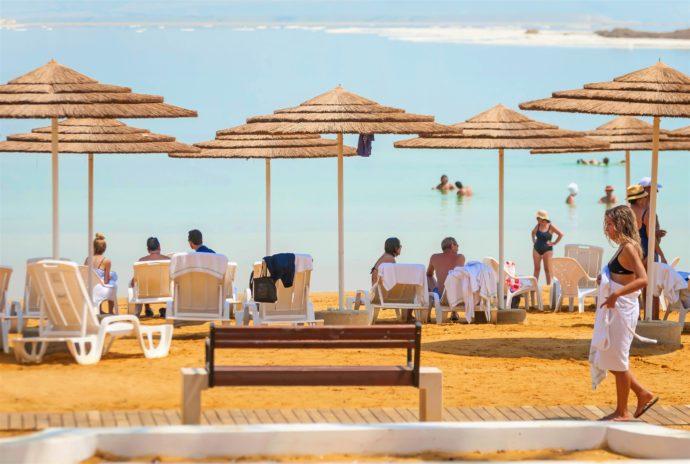 people sitting under umbrellas at dead sea beach